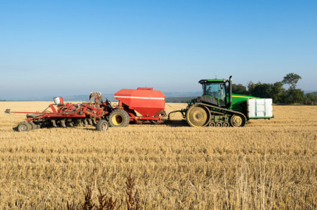 A tractor with other machinery in a stubble field