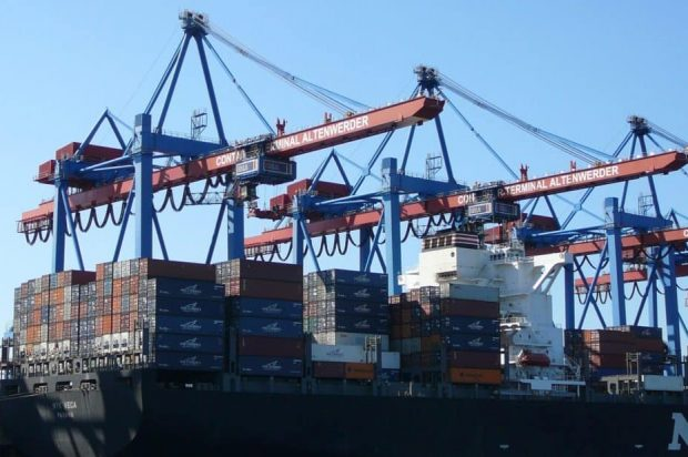 Large cranes load a container ship