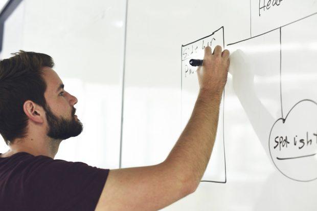 An apprentice draws on a white board