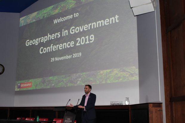 "Man on stage talking in a mic. Text on screen says ""Welcome to Geographers in Government Conference 2019 29th November 2019"". With a Geography logo showing in the bottom left of the screen."