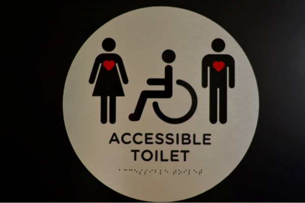Image shows a female, a person in a disabled access vehicle and a male.i
